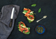 Sandwiches with smoked salmon, avocado, spinach, caper and basil over dark slate stone background. Royalty Free Stock Photography