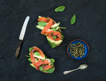 Sandwiches with smoked salmon, avocado, spinach, caper and basil over dark slate stone background. Royalty Free Stock Photo