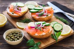 Sandwiches with smoked salmon, red onion, capers, cucumber and lemon. On rustic wooden background. Selective focus Royalty Free Stock Image