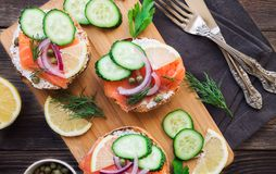 Sandwiches with smoked salmon, red onion, capers, cucumber and lemon. On rustic wooden background. Top view Stock Photography