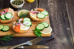 Sandwiches with smoked salmon, red onion, capers, cucumber and lemon. On rustic wooden background Stock Photography