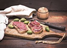 Sandwiches with smoked sausage salami and jamon. On a wooden kitchen board Stock Photos