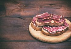 Sandwiches with smoked sausage salami and pieces of hamon. On a round wooden board, empty space on the left Royalty Free Stock Photos
