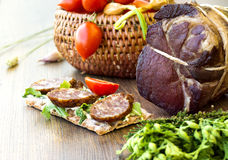 Sandwiches with smoked sausages, gammon, greens and cherry tomatoes in basket Royalty Free Stock Photos