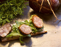 Sandwiches with smoked sausages and gammon, juniper, greens Stock Photography