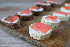 Sandwiches with soft cheese and salmon. On a wooden board Stock Photo