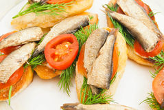 Sandwiches with sprats on dish. Some sandwiches with sprats on a dish royalty free stock image