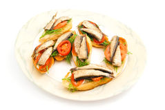 Sandwiches with sprats on plate. Some sandwiches with sprats on a dish on white closeup stock photos