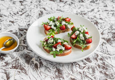 Sandwiches with strawberries, arugula and blue cheese on a white ceramic plate, on a light background. Delicious snack, breakfast or  appetizer with wine Stock Image