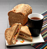 Sandwiches and teamug. Sandwiches and tea mug on porcelain table. Striped napkin and wheat bread in the background Stock Image