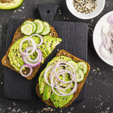 Sandwiches on toast grain dark bread with slices of avocado, sweet pink onions and multi-colored sesame seeds. Top view Royalty Free Stock Image