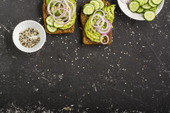 Sandwiches on toast grain dark bread with slices of avocado, sweet pink onions and multi-colored sesame seeds. Top view Stock Images