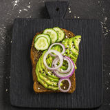 Sandwiches on toast grain dark bread with slices of avocado, sweet pink onions and multi-colored sesame seeds. Top view Stock Image