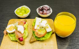 Tasty and nutritious breakfast. Sandwiches with vegetables, eggs, cheese and salmon, and grape and a glass of orange juice. That is a tasty and nutritious Stock Images