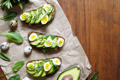 Sandwiches of whole wheat bread with avocado, spinach, guacamole and quail eggs on parchment. Royalty Free Stock Image