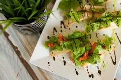 Sandwichies su un piatto bianco su una tavola di legno fotografia stock libera da diritti