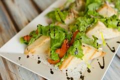 Sandwichies su un piatto bianco su una tavola di legno fotografie stock