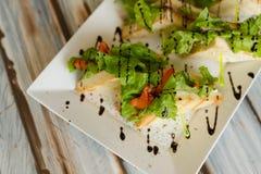 Sandwichies su un piatto bianco su una tavola di legno immagini stock