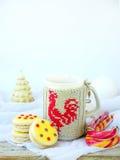 Sandwichkekse mit der gelben Zuckerglasur besprüht mit Zuckersternen und Tasse Tee auf hellem hölzernem Hintergrund Stockbilder