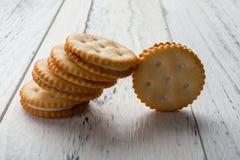 Sandwichkoekjes met het witte room vullen op wit hout Royalty-vrije Stock Foto's