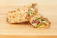 Sandwichomslagen op een raad Stock Foto's