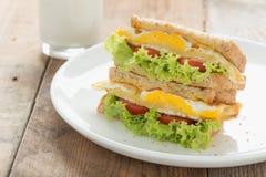 Sandwichs煎蛋用乳酪和牛奶在木头 免版税库存图片