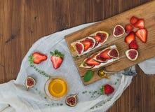 Sandwichs à fromage de chèvre de figue et de fraise avec du miel Images libres de droits