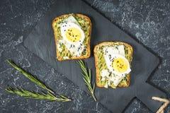 Sandwichs à oeufs et à avocat avec le fromage fondu pour le petit déjeuner sain sur le fond en pierre image stock