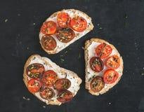 Sandwichs à Ricotta et à cerise-tomate avec le thym frais au-dessus d'un dar Photographie stock