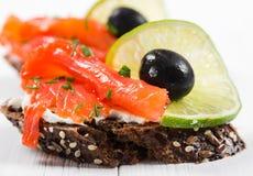 Sandwichs avec des saumons, des olives et la chaux Photographie stock libre de droits