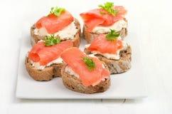 Sandwichs avec des saumons du plat blanc Photographie stock