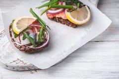Sandwichs avec des saumons, harengs, citron sur un fond blanc Photographie stock