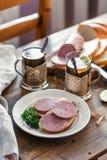 Sandwichs avec la saucisse coupée en tranches d'un plat avec le thé Photographie stock libre de droits