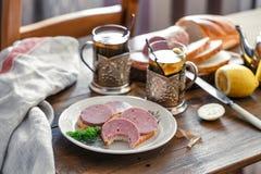 Sandwichs avec la saucisse coupée en tranches d'un plat avec le thé Images libres de droits
