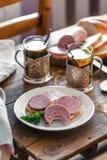 Sandwichs avec la saucisse coupée en tranches d'un plat avec le thé Photographie stock