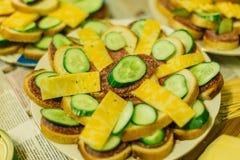 Sandwichs avec la saucisse et le fromage et les concombres d'un plat photos stock