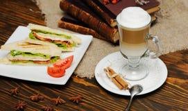 Sandwichs avec le poulet, la tomate et la salade sur un fond en bois sur un fond de latte et de vieux livres Photos stock