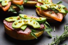 Sandwichs avec le salami, l'avocat et les herbes photos stock