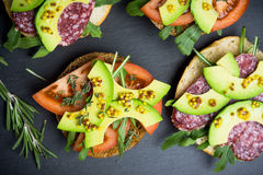 Sandwichs avec le salami, l'avocat et les herbes Image stock