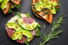 Sandwichs avec le salami, l'avocat et les herbes Photographie stock