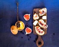 Sandwichs avec les figues, le fromage de chèvre, le miel et les myrtilles frais sur le conseil en bois Nourriture végétarienne, c image libre de droits