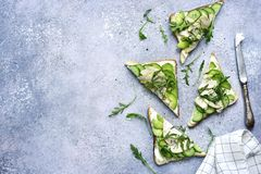 Sandwichs com queijo macio, abacate, pepino, rúcula e grade Imagens de Stock