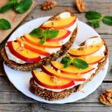 Sandwichs doux de noix et fondu à fromage de nectarine, Sandwichs ouverts à pain de Rye avec le fromage fondu, nectarine mûre, no Photo stock