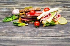 Sandwichs frais avec le salami, les légumes, le jambon et le fromage sur une table en bois Images libres de droits