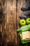 Sandwichs, fruit, milkshake et espadrilles de sports Photo stock