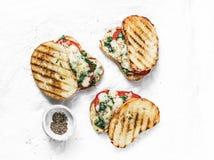 Sandwichs grillés chauds à tomates, à épinards et à mozzarella - petit déjeuner sain, casse-croûte, tapas, apéritifs sur un fond  image libre de droits