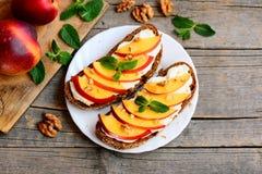 Sandwichs sains de noix et fondu à fromage de nectarine, Sandwichs ouverts avec le fromage fondu, tranches mûres de nectarine, no Photo stock