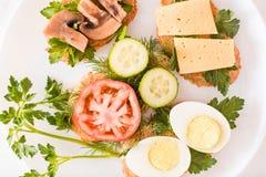 Sandwichs savoureux d'un plat et fourchettes sur une table Images stock