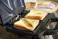 Sandwichtoaster mit Toast Stockfoto