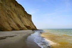 Sandy abandonó la playa con los acantilados Orilla de mar Foto de archivo libre de regalías